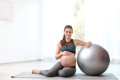 Jonge zwangere vrouw in geschiktheidskleren met oefeningsbal thuis stock fotografie