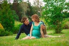 Jonge zwangere vrouw met de jonge mens in het park Stock Afbeelding
