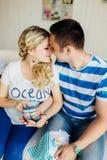 Jonge zwangere vrouw met echtgenoot op witte bank in de babyschoenen van de ruimtegreep Stock Foto's