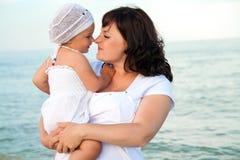 Jonge zwangere vrouw met haar dochter op het strand. Royalty-vrije Stock Fotografie