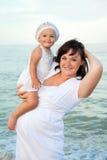 Jonge zwangere vrouw met haar dochter op het strand. Stock Fotografie