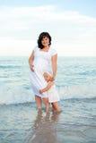 Jonge zwangere vrouw met haar dochter op het strand. Stock Afbeelding