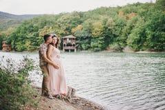 Jonge zwangere vrouw met haar echtgenoot die zich dichtbij meer bevinden Stock Afbeeldingen