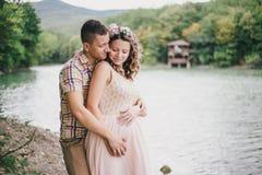 Jonge zwangere vrouw met haar echtgenoot die zich dichtbij meer bevinden Stock Afbeelding