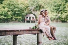 Jonge zwangere vrouw met haar echtgenoot die zich dichtbij meer bevinden Royalty-vrije Stock Afbeeldingen