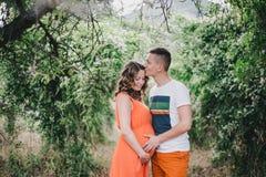 Jonge zwangere vrouw met haar handen van de echtgenootholding op haar buik Royalty-vrije Stock Foto's