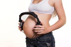 Jonge zwangere vrouw met oortelefoons op de buik Stock Foto's