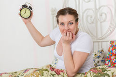 Jonge zwangere vrouw met wekker. stock fotografie