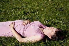 Jonge zwangere vrouw in park Royalty-vrije Stock Afbeeldingen