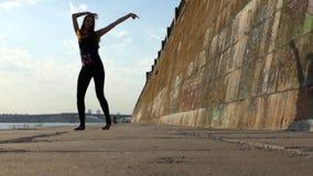 Jonge Zwangere Vrouw in Zwarte Kostuumdansen op Riverbank op Sunny Day in slo-Mo stock footage