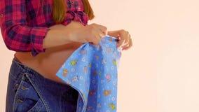 Jonge zwangere vrouwen die inwikkelend kleren voor de geboorte van baby voorbereidingen treffen Zwangerschap en moederschapconcep stock video