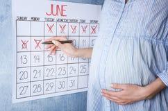 Jonge zwangere vrouwen tellende dagen met kalender stock fotografie