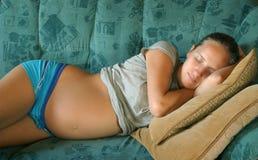 Jonge zwangere vrouwenslaap Stock Afbeeldingen