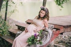 Jonge zwangere vrouwenzitting dichtbij meer Stock Fotografie