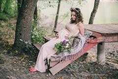 Jonge zwangere vrouwenzitting dichtbij meer Royalty-vrije Stock Fotografie