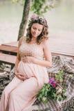 Jonge zwangere vrouwenzitting dichtbij meer Royalty-vrije Stock Foto