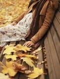 Jonge zwangere vrouwenzitting op een bank in het park in de herfst met vele gele bladeren royalty-vrije stock foto