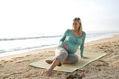 Jonge zwangere vrouwenzitting op mat bij strand stock afbeelding