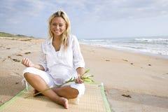 Jonge zwangere vrouwenzitting op strand stock foto