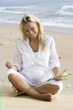 Jonge zwangere vrouwenzitting op strand royalty-vrije stock afbeelding