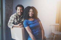 Jonge zwarte Afrikaanse mens en zijn meisje bewegende dozen in nieuw huis samen en makend het mooi leven vrolijk Royalty-vrije Stock Afbeeldingen