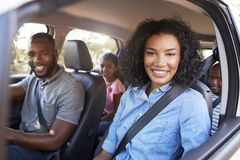 Jonge zwarte familie in een auto op een wegreis die aan camera glimlachen royalty-vrije stock foto's