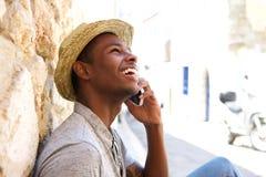 Jonge zwarte mens die en op mobiele telefoon glimlachen spreken Royalty-vrije Stock Foto