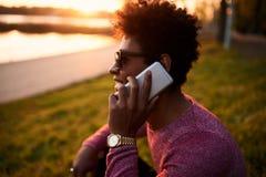 Jonge zwarte mens die en op slimme telefoon glimlachen spreken Royalty-vrije Stock Foto