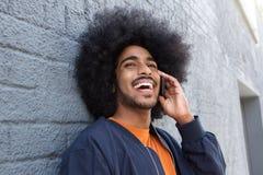 Jonge zwarte mens die met afro op mobiele telefoon spreken Stock Afbeeldingen