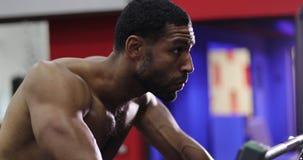 Jonge zwarte mens die tussen oefeningen in de gymnastiek rusten stock videobeelden