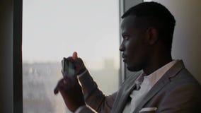 Jonge zwarte mens in kostuum die smartphone gebruiken die zich door venster in gettobureau bevinden in de zon stock video