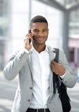Jonge zwarte mens met zak die op mobiele telefoon spreken Stock Fotografie
