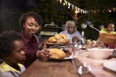 Jonge zwarte moeder die haar zoonsvoedsel dienen bij een familiebarbecue royalty-vrije stock foto's