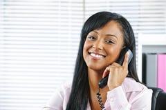 Jonge zwarte onderneemster die op telefoon spreekt Stock Foto