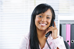 Jonge zwarte onderneemster die op telefoon spreekt stock afbeelding