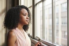 Jonge zwarte onderneemster die uit venster kijken royalty-vrije stock afbeelding