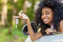 Jonge zwarte tiener de autosleutels die van de bestuurdersholding haar nieuwe auto drijven Stock Foto