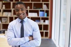 Jonge zwarte zakenman die aan camera in een bestuurskamer glimlachen stock foto