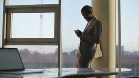 Jonge zwarte zakenman in kostuum die smartphone gebruiken die zich door venster in bureau in de zon bevinden stock footage
