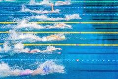 Jonge zwemmers in openlucht zwembad tijdens de concurrentie Gezondheid en geschiktheidslevensstijlconcept met jonge geitjes Royalty-vrije Stock Foto's