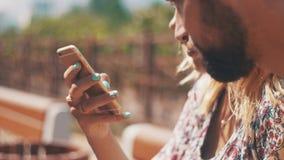 Jongelui in de zitting van het gebruikssmartphone van het liefdepaar op bank De zonnige dag van de zomer stock videobeelden