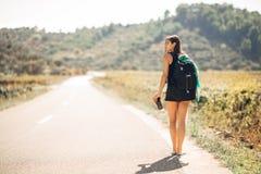 Jongelui die avontuurlijke vrouw lift op de weg backpacking Reizend rugzakkenvolume, verpakkingshoofdzaak Reislevensstijl Stock Fotografie
