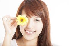 Jongelui die Aziatische vrouw met bloem glimlachen Stock Afbeelding