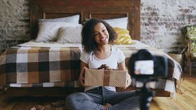 Jongelui die de Afrikaanse videoblog van de meisjesopname over de giftdoos van verpakkingskerstmis thuis glimlachen Royalty-vrije Stock Foto's