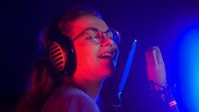 Jongelui die emotionele vrouw in glazen glimlachen die in T.L.-verlichting in de studio zingen royalty-vrije stock foto's