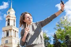 Jongelui die Europese vrouw glimlachen die zelf-portretbeeld met gemakkelijk behandelde camera nemen tegen klokketoren van kerk i stock afbeeldingen