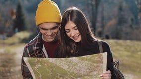 Jongelui die gelukkig paar glimlachen die zich in de bergen bevinden Zij die van hun wandeling genieten Het kijken op toeristenka stock videobeelden