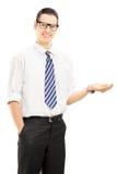 Jongelui die het mannelijke gesturing met zijn hand glimlachen Royalty-vrije Stock Foto's