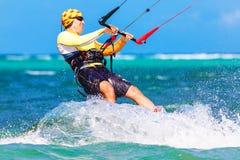 Jongelui die kitesurfer op overzeese Extreme Sport als achtergrond Kitesur smiing Royalty-vrije Stock Afbeeldingen