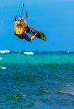 Jongelui die kitesurfer op overzeese Extreme Sport als achtergrond Kitesur smiing Stock Afbeeldingen